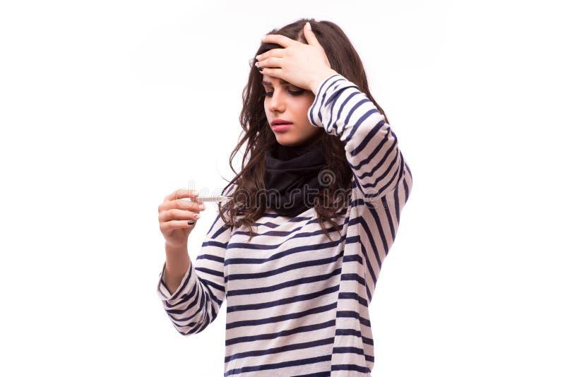 Молодая больная женщина в шарфе и домашних одеждах смотря термометр стоковые изображения