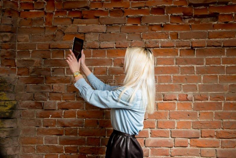 Молодая блондинка делает selfie Selfshot outdoors против красной кирпичной стены стоковая фотография