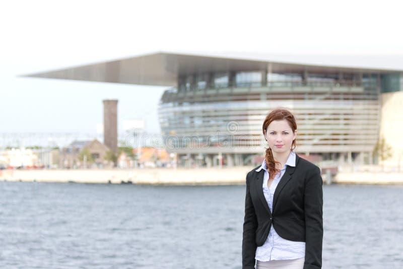 Молодая взрослая бизнес-леди стоя в районе гавани стоковое фото rf
