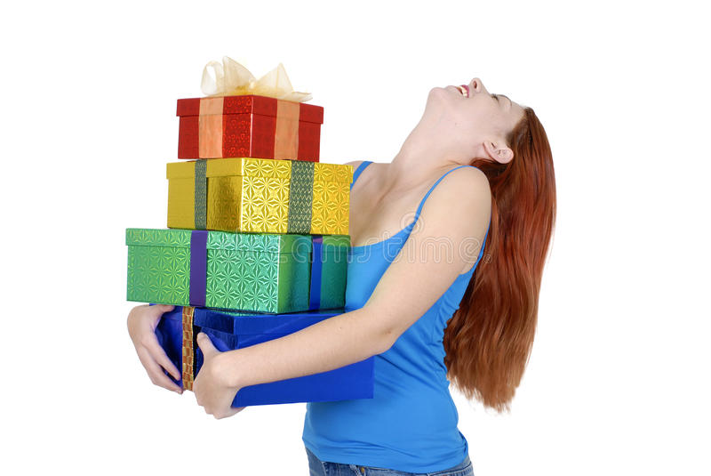 Молодая взрослая женщина в вскользь одеждах держа или нося малую кучу рождества или подарков на день рождения стоковая фотография