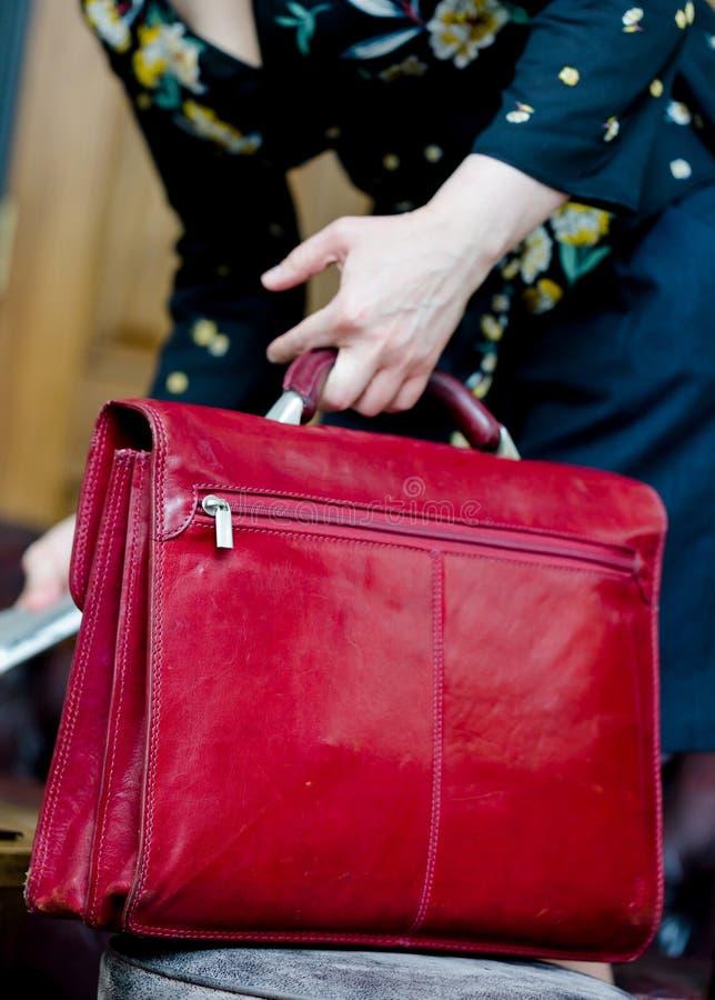 Молодая взрослая женщина держит красную кожаную сумку компьтер-книжки стоковое изображение