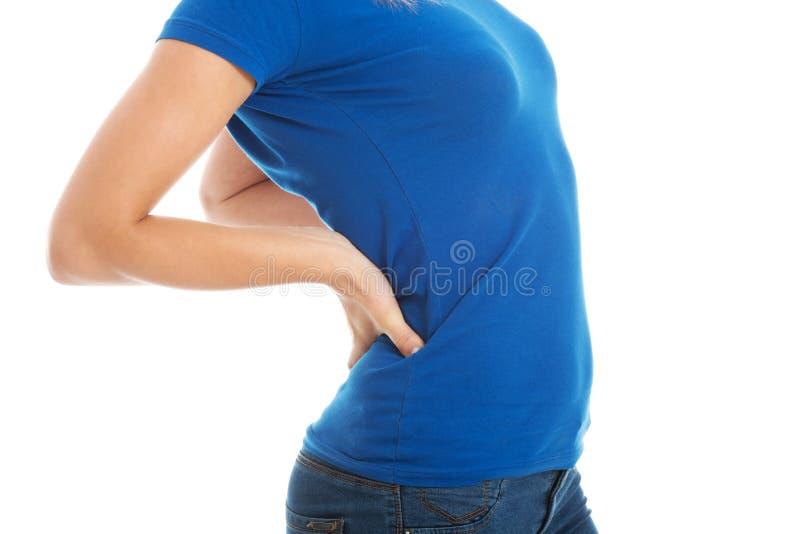 Молодая вскользь женщина имеет backpain. стоковые изображения rf