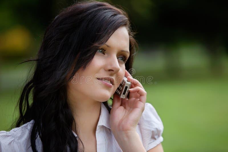 Молодая вскользь женщина на звонке стоковое изображение