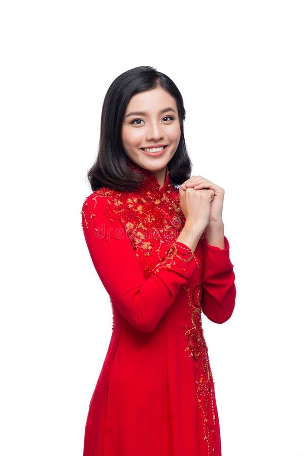 Молодая въетнамская женщина в платье Ao Dai с моля желанием жеста стоковая фотография rf