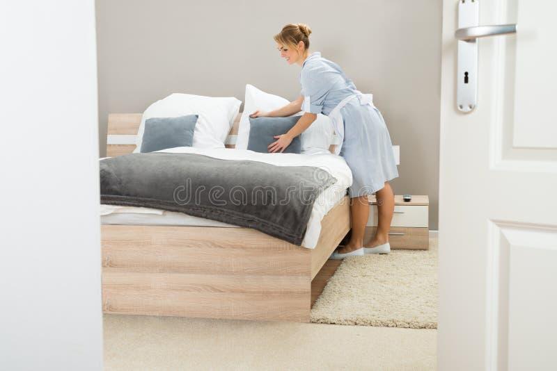 Молодая горничная аранжируя подушку на кровати стоковые изображения rf