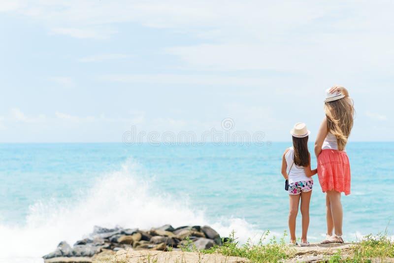 Молодая европейская женщина и ее маленькая сестра дочери или молодых остающся и держащ руками одина другого на береге голубого se стоковая фотография
