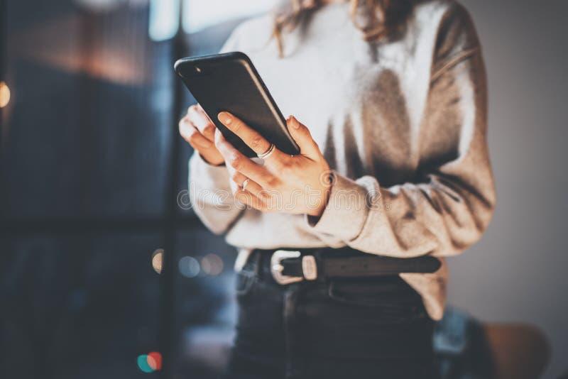 Молодая девушка битника держа современный smartphone в руках и касающем экране Горизонтальная, запачканная предпосылка, влияния b стоковые изображения rf