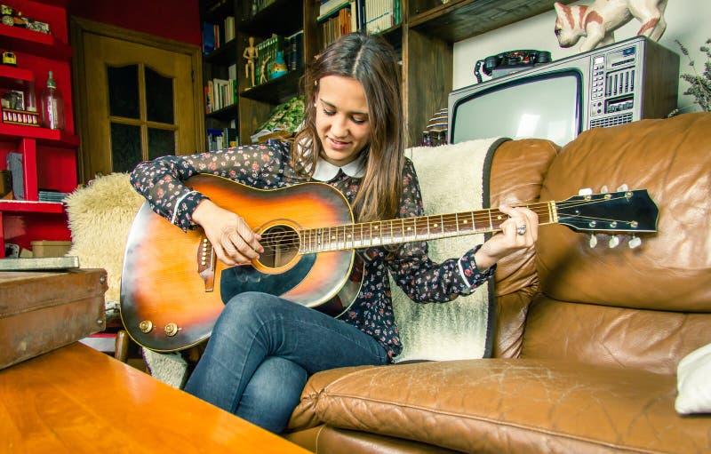 Молодая девушка битника играя акустическую гитару дома стоковое фото