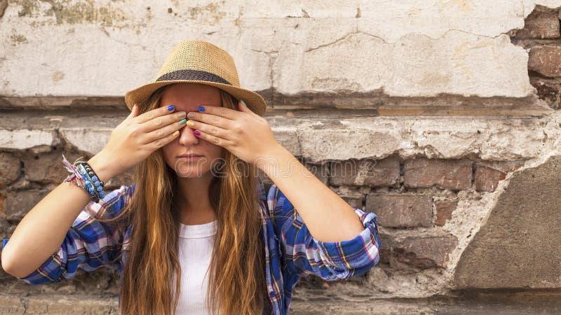 Молодая девушка битника стоя в городке улицы старом и закрывает его глаза его руки с покрашенными ногтями стоковое изображение rf