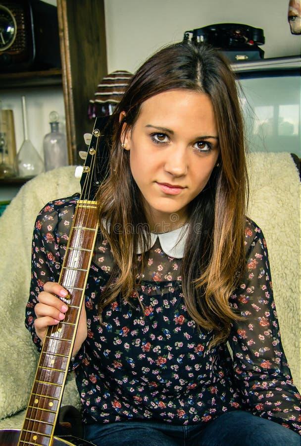 Молодая девушка битника с акустической гитарой дома стоковое фото rf