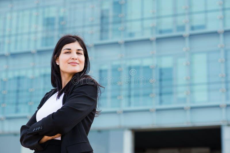 Молодая девушка брюнет усмехаясь с пересеченными оружиями перед buil стоковая фотография