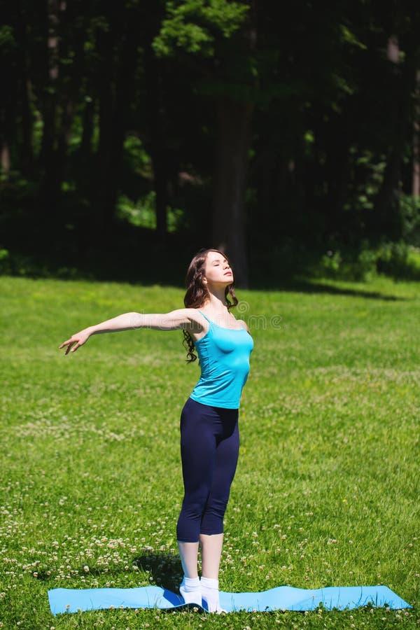Молодая девушка спорта делает йогу в парке стоковое изображение rf