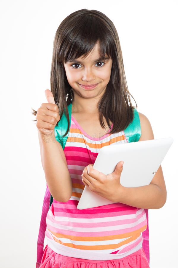 Молодая девушка школы при таблетка и schoolbag показывая большие пальцы руки вверх стоковые изображения