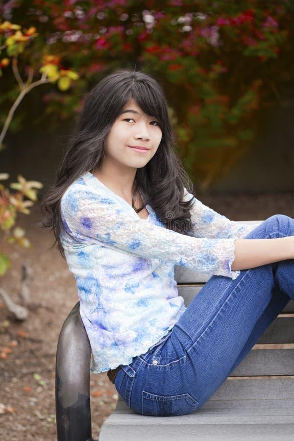 Молодая девушка preteen сидя на скамейке в парке outdoors стоковые фото