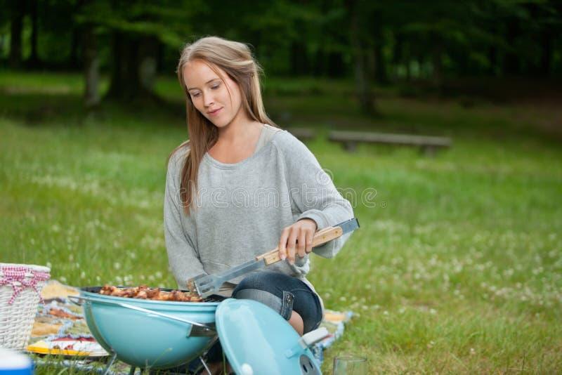 Молодая женская варя еда на барбекю стоковые изображения