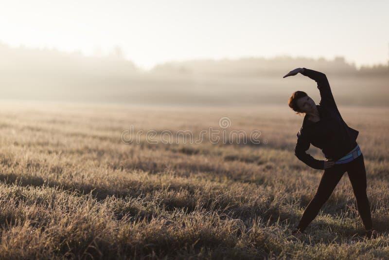 Молодая женская делая йога в утре стоковая фотография