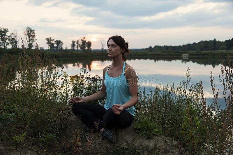 Молодая женская делая йога озером стоковое изображение