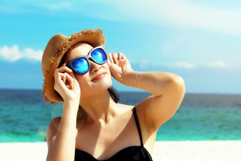 Молодая женская фотомодель усмехаясь и нося большие солнечные очки на пляже стоковое изображение