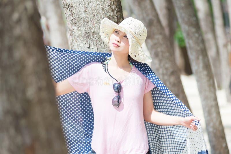 Молодая женщина Азии стоя с сосной на пляже стоковая фотография