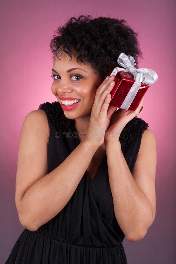 Молодая женщина афроамериканца держа подарок стоковые фотографии rf