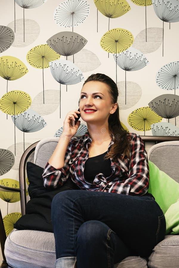 Молодая женщина бара умная вскользь говоря на smartphone стоковое фото