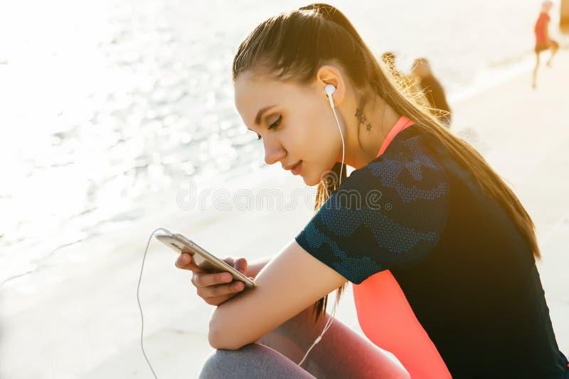 Молодая женщина бегуна ослабляет, утомляла после jogging на улице, реке co стоковые фотографии rf