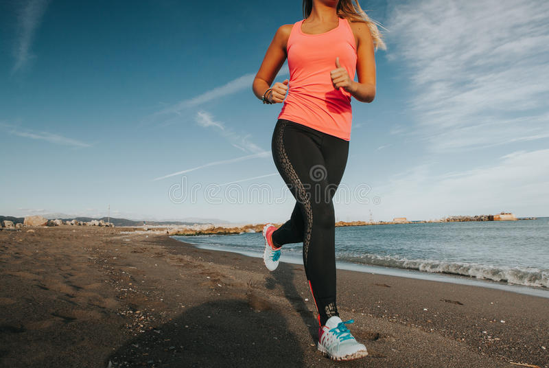 Молодая женщина бежать на пляже стоковые фото