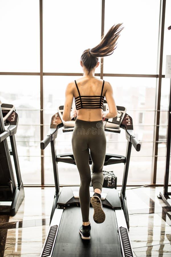 Молодая женщина бежать на третбане в спортзале стоковое фото rf