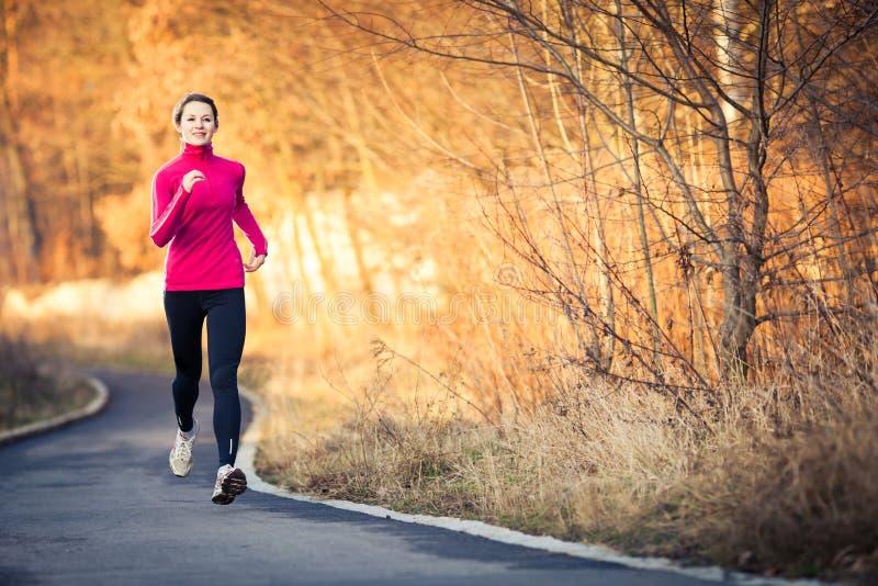 Молодая женщина бежать outdoors в парке города стоковые изображения rf