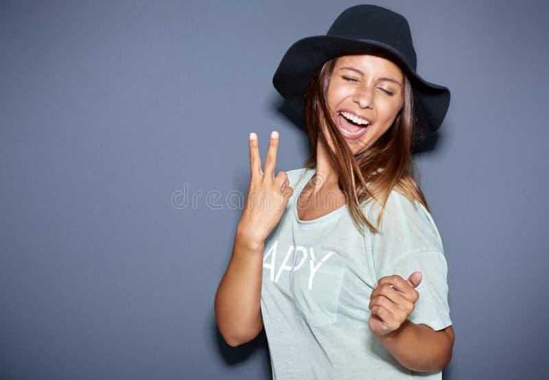 Молодая женщина битника модная давая V-знак стоковые фото