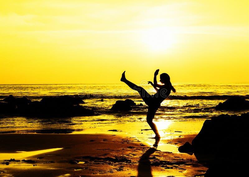 Молодая женщина бокса пинком на пляже стоковые изображения
