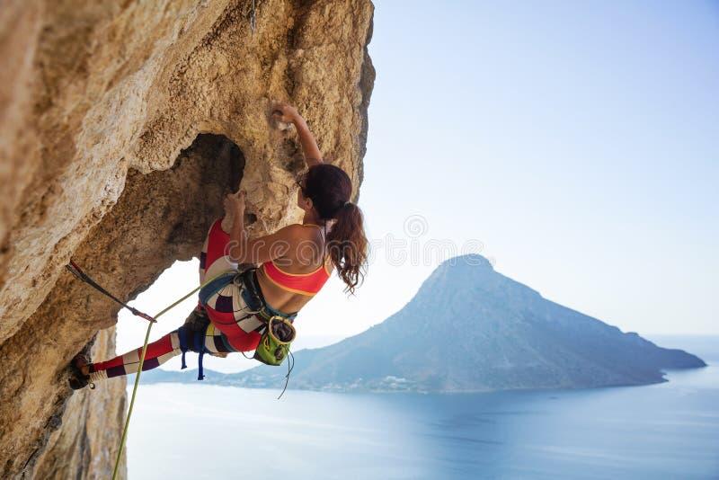 Молодая женщина борясь для того чтобы взобраться уступ на скале стоковые изображения rf