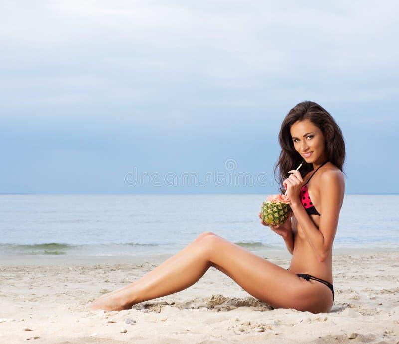Молодая женщина брюнет в купальнике выпивая коктеил стоковые изображения rf