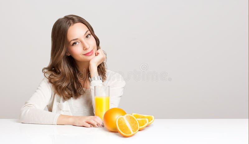 Молодая женщина брюнет имея апельсиновый сок стоковые фотографии rf