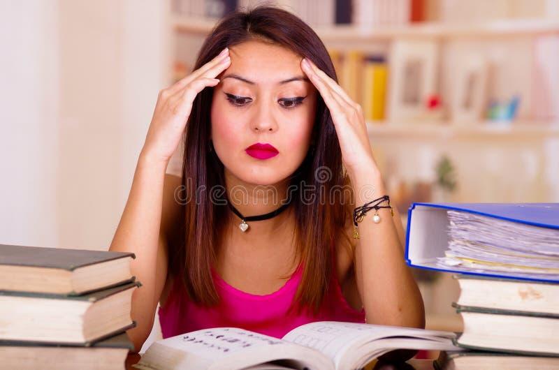 Молодая женщина брюнет нося розовую верхнюю часть сидя столом с стогом книг помещенных на ей, держащ руки на голову, утомляла стоковое фото rf