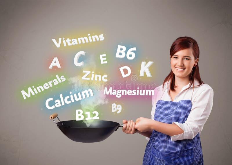 Молодая женщина варя витамины и минералы стоковые изображения rf