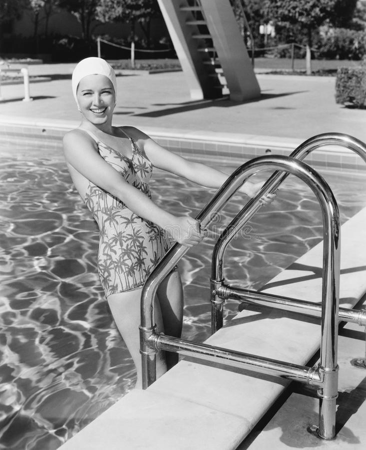 Молодая женщина взбираясь вверх лестница бассейна (все показанные люди более длинные живущие и никакое имущество не существует по стоковая фотография rf