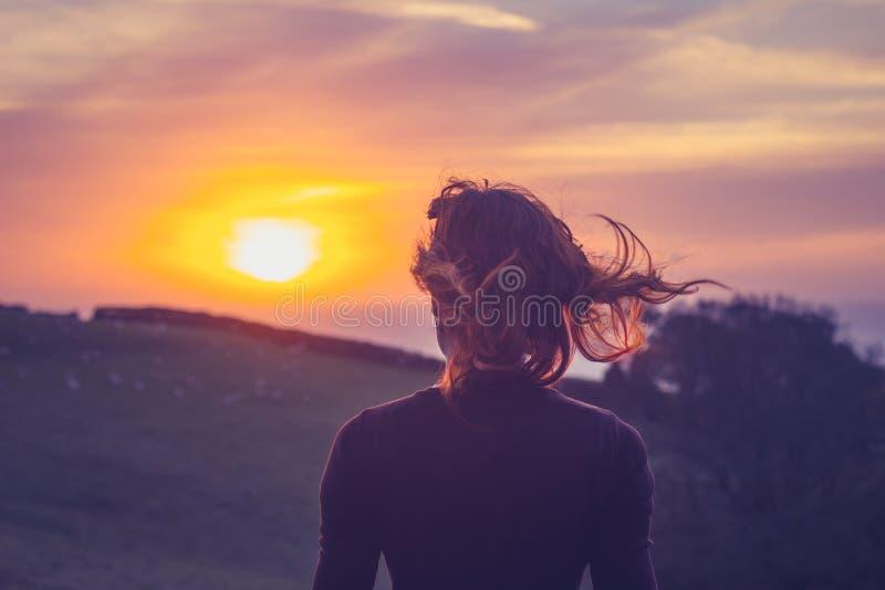Молодая женщина восхищая заход солнца над полями стоковые изображения rf