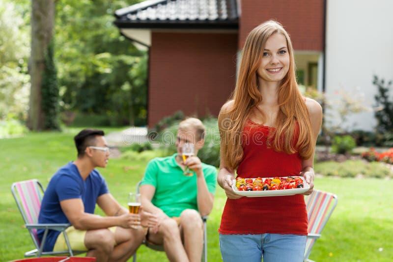 Молодая женщина во время приём гостей в саду стоковая фотография