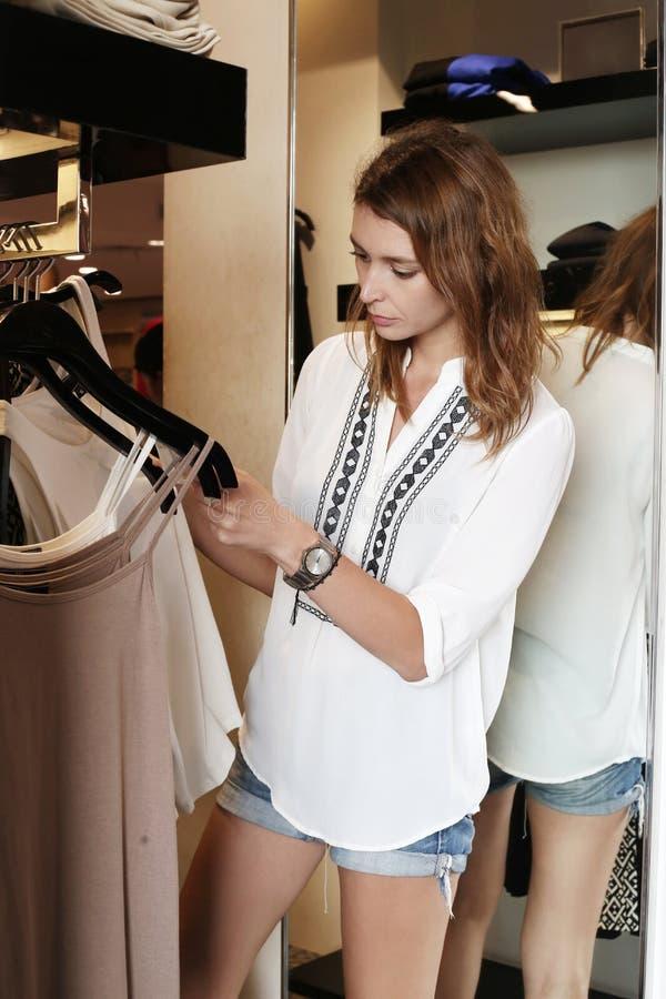 Молодая женщина выбирает одежды стоковые изображения rf
