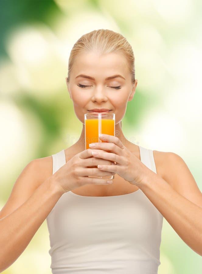 Молодая женщина выпивая апельсиновый сок стоковые изображения