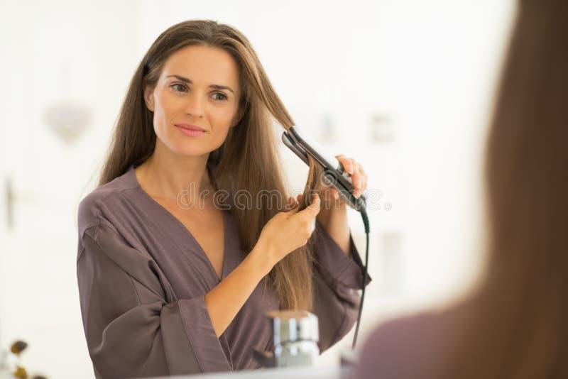 Молодая женщина выправляя волосы в ванной комнате стоковая фотография rf