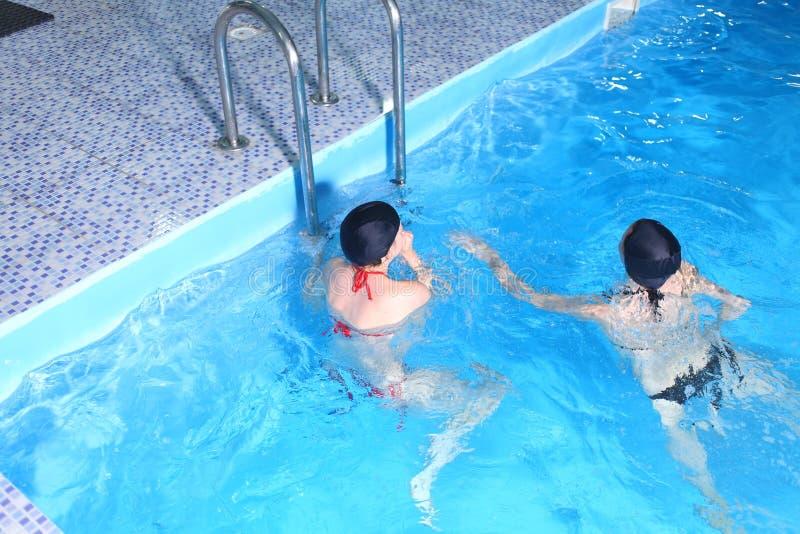 Молодая женщина в бассейне имея потеху стоковая фотография