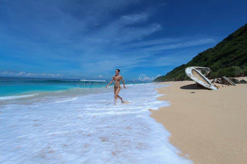 Молодая женщина в бегах бикини вдоль пляжа океана в tropocal стоковое изображение rf