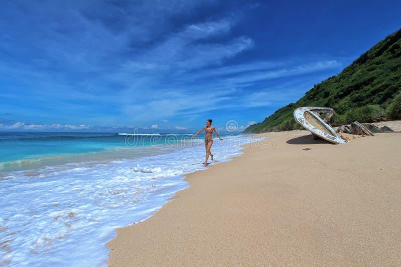 Молодая женщина в бегах бикини вдоль пляжа океана в tropocal стоковая фотография