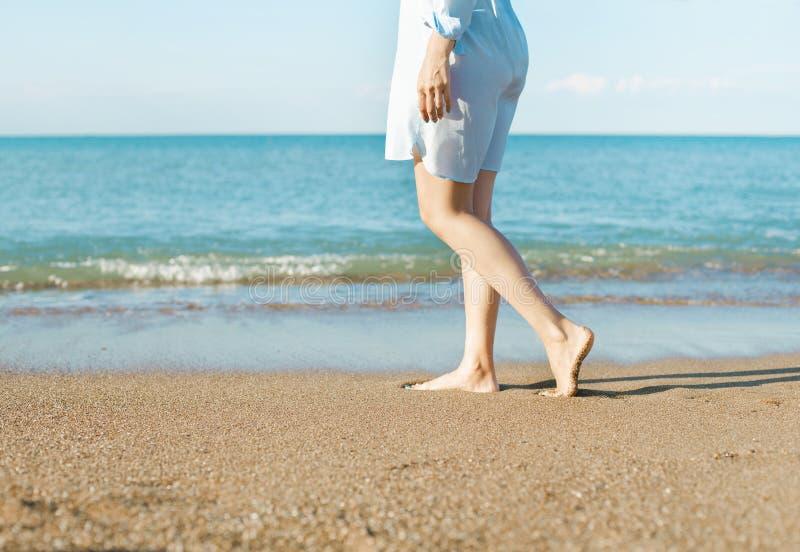 Молодая женщина в белом платье идя на пляж стоковое фото rf