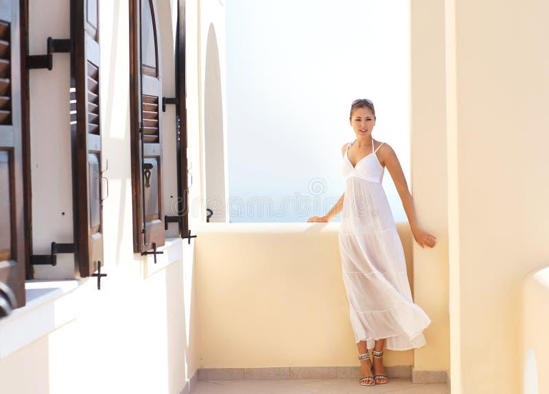 Молодая женщина в белом платье на каникуле стоковые фото