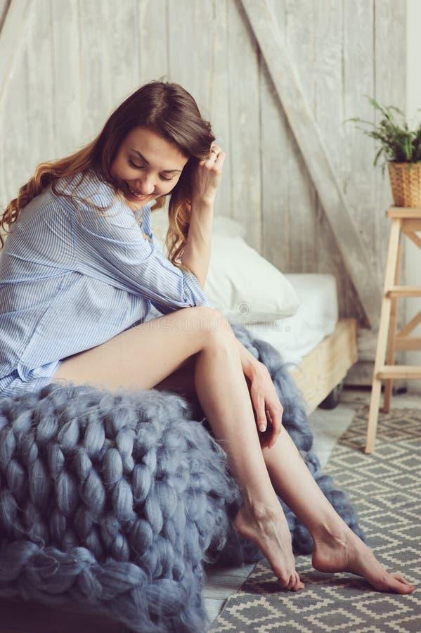 Молодая женщина в бодрствовании пижамы вверх в утре в уютной скандинавской спальне и лежать на кровати с сверхразмерным связанным стоковые фотографии rf