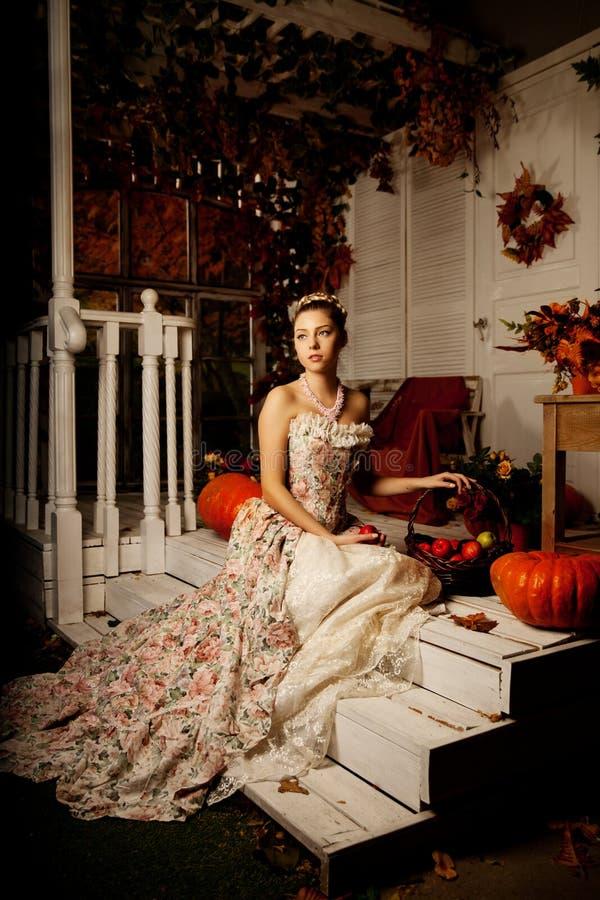 Молодая женщина в винтажном платье на крылечке осени Девушка красоты в fa стоковая фотография rf