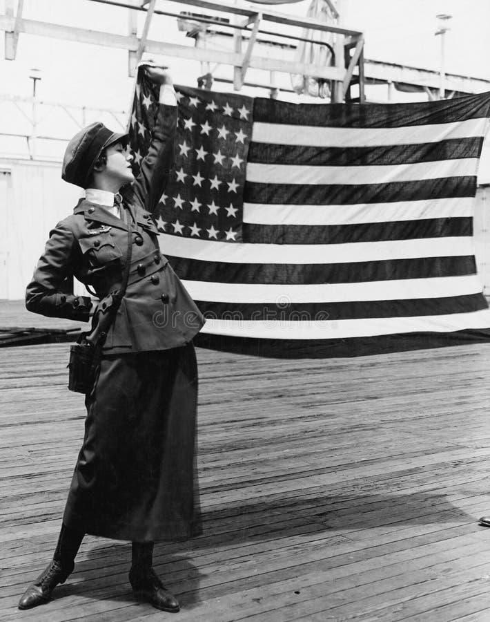 Молодая женщина в военной форме задерживая американский флаг (все показанные люди более длинные живущие и никакое имущество не су стоковые фото